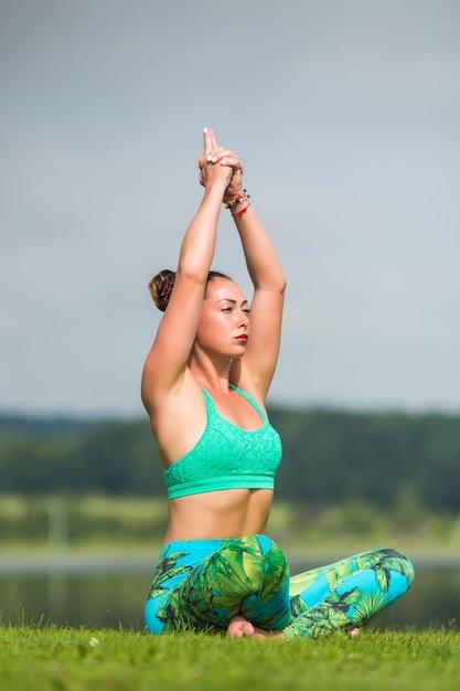Mooie vrouw doet yoga oefeningen in het groene park Gratis Foto