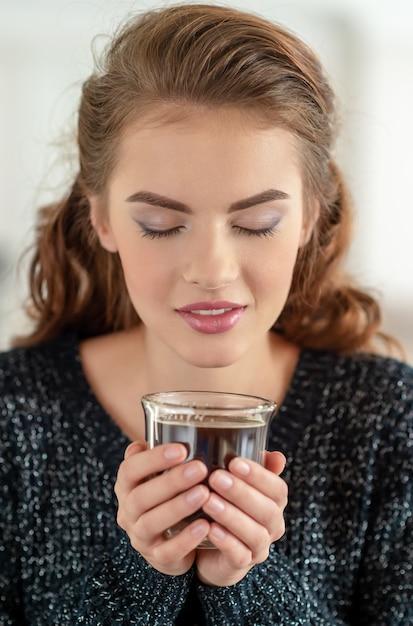 Mooie vrouw drinkt koffie en geniet van de smaak. vrij jong volwassen meisje ontspannen met een kopje thee. Gratis Foto