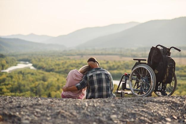 Mooie vrouw en haar wilsonbekwame echtgenoot rusten samen in de buurt van zijn rolstoel op de heuvel. Premium Foto