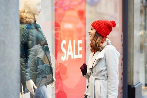 Mooie vrouw etalage kijken tijdens het winkelen Gratis Foto