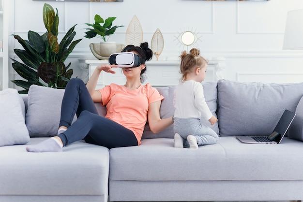 Mooie vrouw gebruikt virtual reality-bril thuis op de bank terwijl haar dochter tekenfilms op laptop bekijkt Premium Foto