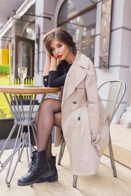 Mooie vrouw gekleed in zwarte jurk en beige loopgraaf met stijlvol kapsel en rode lippen op een terras Gratis Foto
