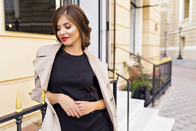 Mooie vrouw gekleed in zwarte jurk en beige loopgraaf met stijlvol kapsel en rode lippen op straat Gratis Foto