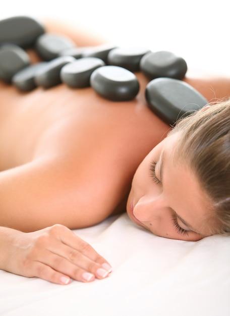 Mooie vrouw geniet van spa met stenen Gratis Foto