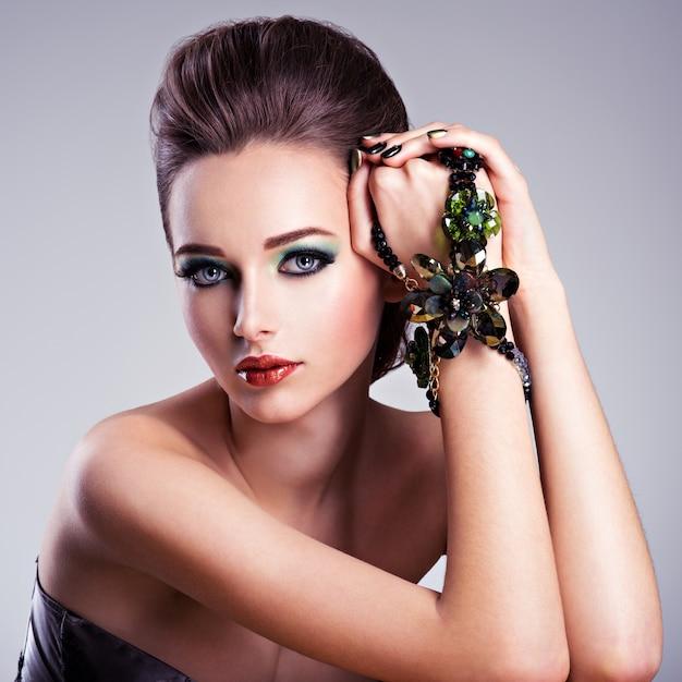 Mooie vrouw gezicht met mode groene make-up en sieraden bij de hand Gratis Foto