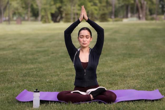 Mooie vrouw het beoefenen van yoga buitenshuis Gratis Foto