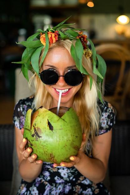 Mooie vrouw het drinken kokosnoot in de tropische koffie Premium Foto