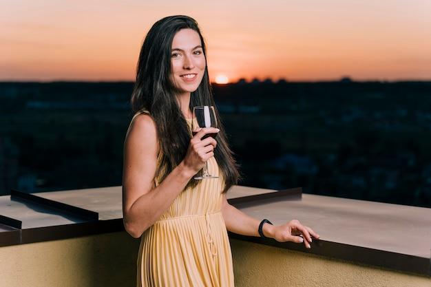 Mooie vrouw het drinken wijn op dak bij dageraad Gratis Foto