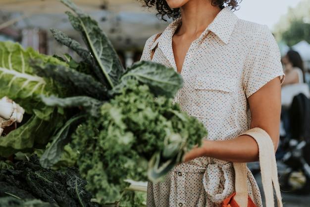 Mooie vrouw het kopen boerenkool bij een landbouwersmarkt Premium Foto