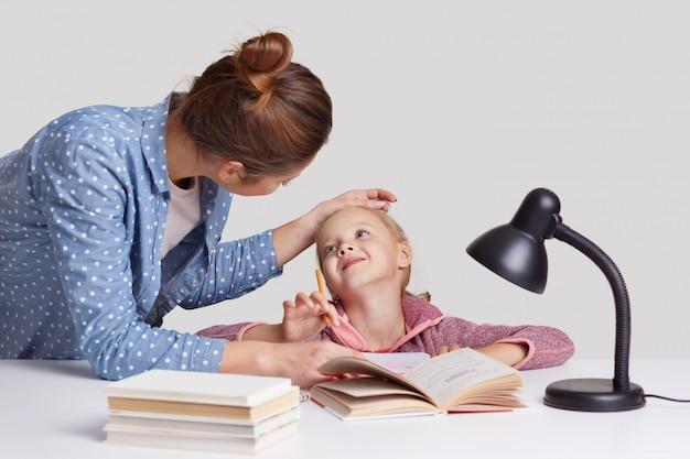 Mooie vrouw houdt dochters voorhoofd bij de hand, prijst en stimuleert haar om goed te studeren, poseert samen op het bureaublad. mooi meisje behaalde uitstekende cijfers op school, wordt geprezen door mama Premium Foto
