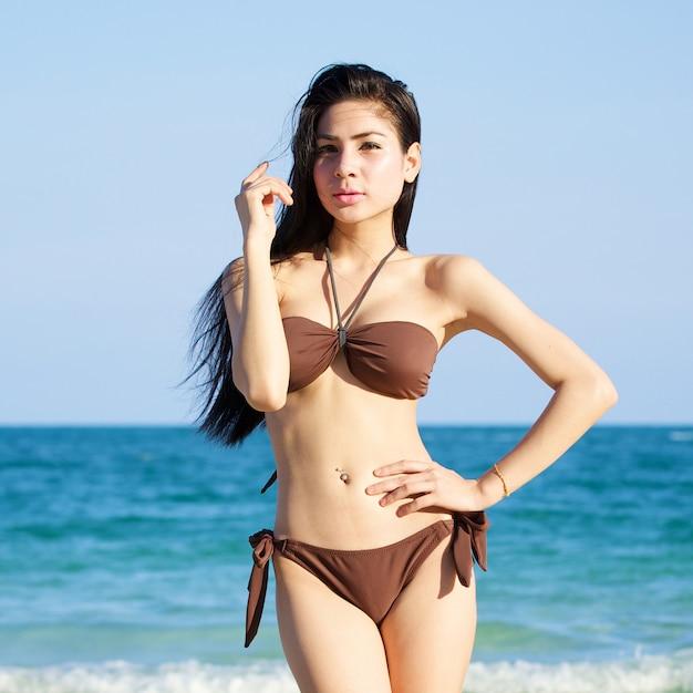 Mooie vrouw in bikini op het strand op zomerdag Premium Foto