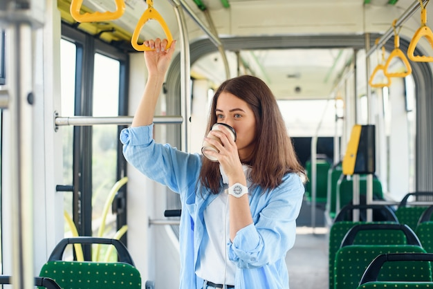 Mooie vrouw in blauwe shit drinkt koffie tijdens het rijden in het openbaar vervoer. Premium Foto