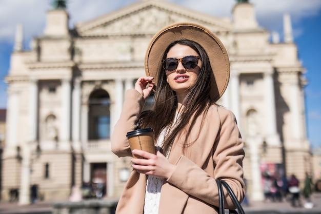 Mooie vrouw in casual herfst kleding poseren in de stad met een koffiekopje in haar handen Gratis Foto