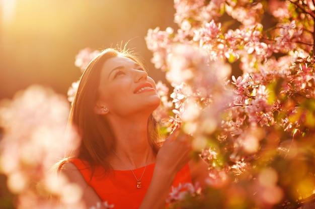 Mooie vrouw in de ruikende tot bloei komende de appelboom van de de zomertuin Premium Foto