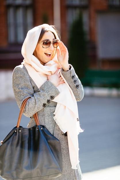 Mooie vrouw in een jas die zich voordeed op straat Gratis Foto
