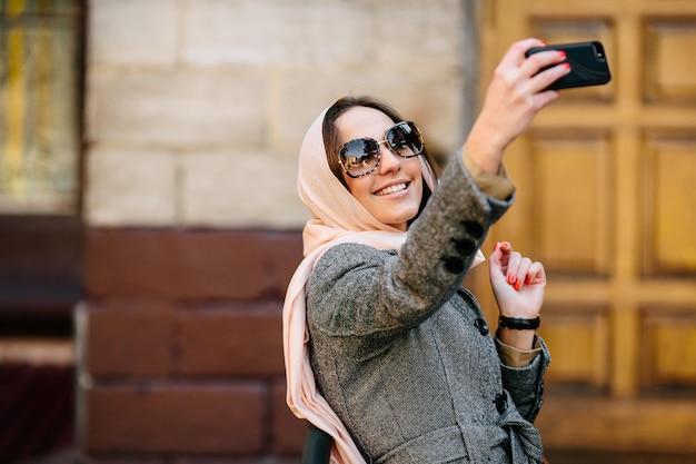 Mooie vrouw in een jas op straat maakt selfie Gratis Foto