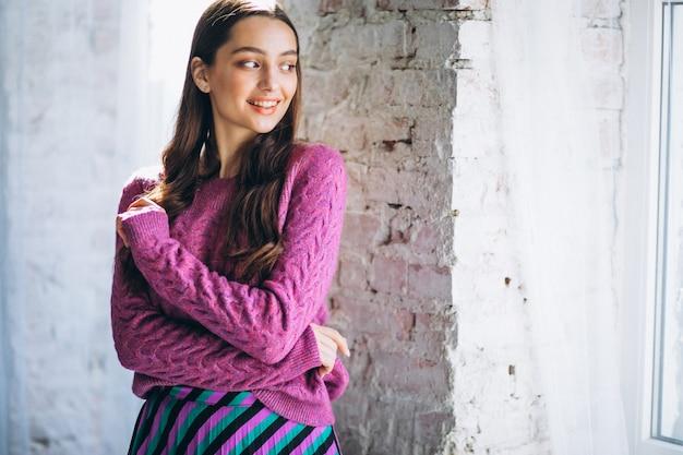 Mooie vrouw in een paarse trui en rok Gratis Foto