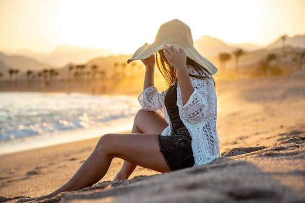 Mooie vrouw in een witte cape met een hoed op haar hoofd die zich voordeed op het strand bij zonsondergang. Gratis Foto