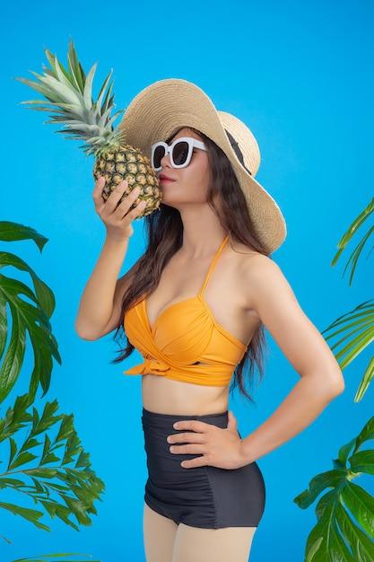 Mooie vrouw in een zwempak die een ananas op blauw houdt Gratis Foto