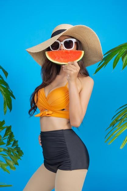 Mooie vrouw in een zwempak die een watermeloen op blauw houden Gratis Foto