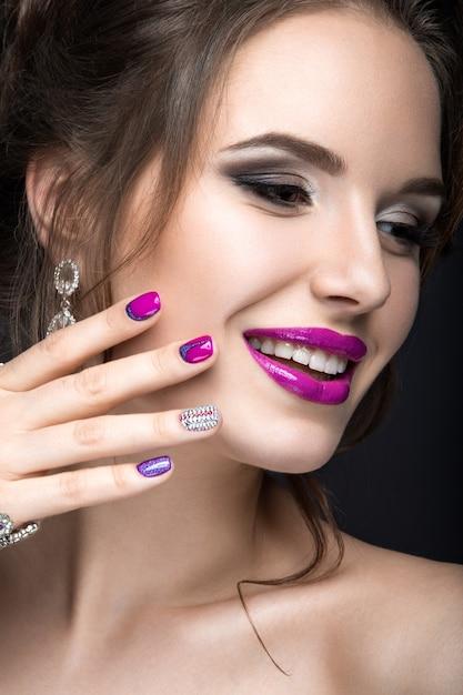 Mooie vrouw in gotische stijl met avondmake-up en rode nagels met doornen. foto genomen in een studio op een rode achtergrond. Premium Foto
