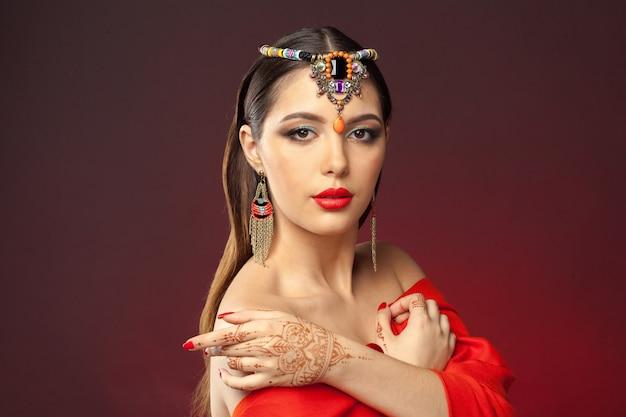 Mooie vrouw in oosterse stijl met mehendi op dark Premium Foto