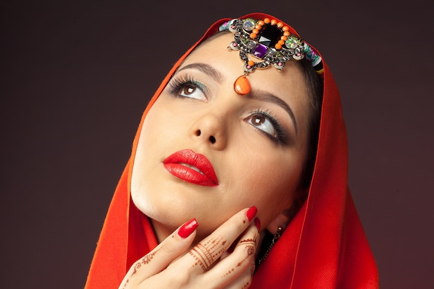 Mooie vrouw in oosterse stijl met mehendi op donker Premium Foto