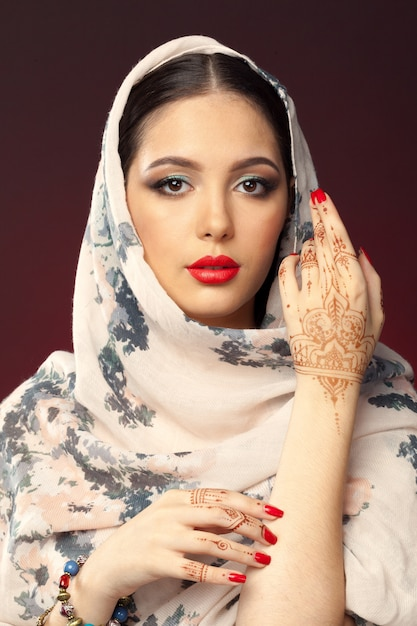 Mooie vrouw in oosterse stijl met mehendi op donkere achtergrond Premium Foto