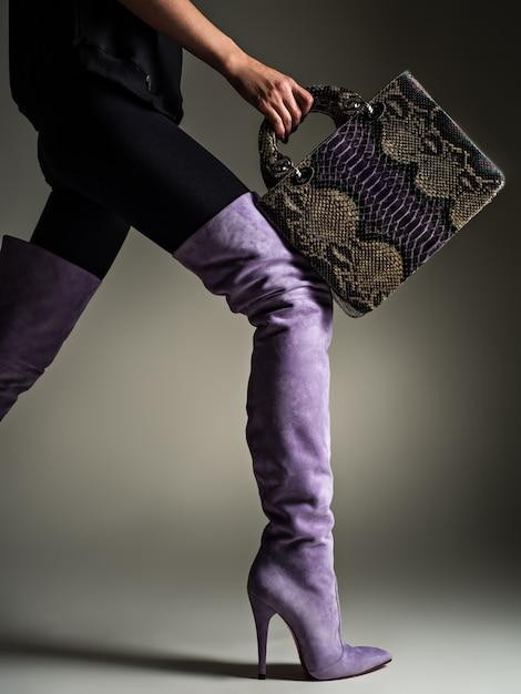 Mooie vrouw in paarse hoge laarzen. modieus meisje houdt stijlvolle violet lederen tas. glamour stijlvol concept. kunst. model loopt na het winkelen. Gratis Foto