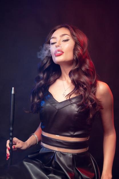 Mooie vrouw in rook waterpijp of shisha. witte wolk vape. Premium Foto
