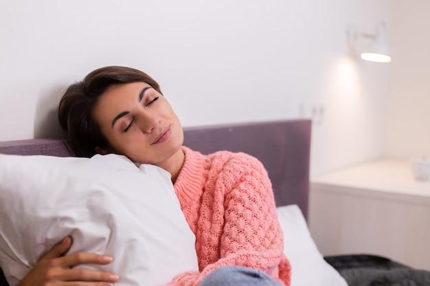 Mooie vrouw in roze schattige gebreide pullover thuis in bed, glimlachen, genieten van tijd alleen Gratis Foto