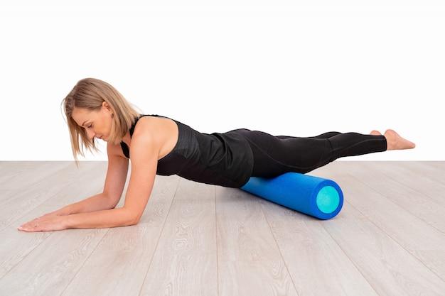 Mooie vrouw in sportkleding, pilates-instructeur die en zich met schuimrol uitrekken opwarmen. de plankoefening met nadruk op de rolgeschiktheid. Premium Foto