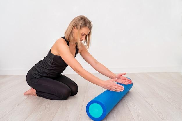 Mooie vrouw in sportkleding, pilates-instructeur die en zich met schuimrol uitrekken opwarmen, met vrije tekstruimte. Premium Foto