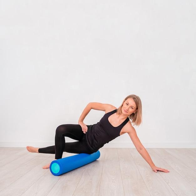 Mooie vrouw in sportkleding, pilates-instructeur die en zich met schuimrol uitrekken opwarmen Premium Foto