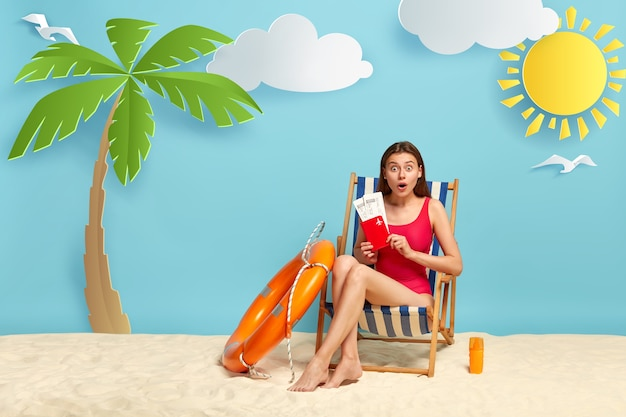 Mooie vrouw in verlegenheid gebracht vliegt kaartjes met paspoort, poseert op de strandstoel, heeft een mooie reis op zee, gekleed in badkleding Gratis Foto