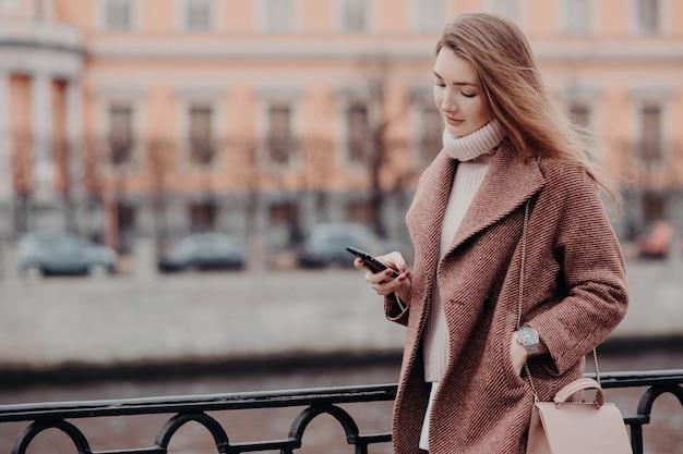 Mooie vrouw in warme jas, houdt moderne mobiele telefoon, berichten in sociale netwerken Premium Foto