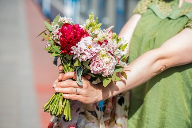 Mooie vrouw in witte jas met rode rozen in de hand Premium Foto