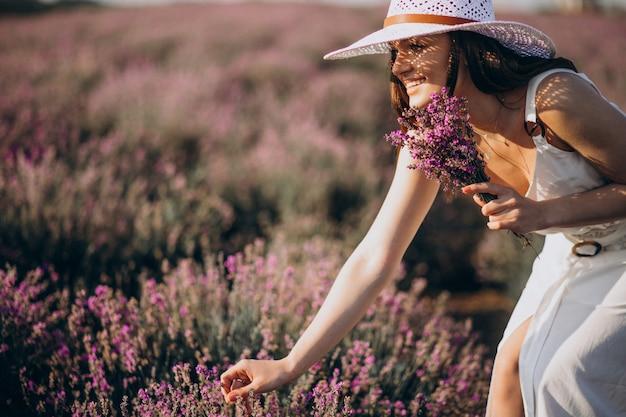 Mooie vrouw in witte jurk in een lavendel veld Gratis Foto