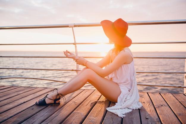 Mooie vrouw in witte jurk zittend aan zee op zonsopgang in romantische sfeer met rode hoed Gratis Foto