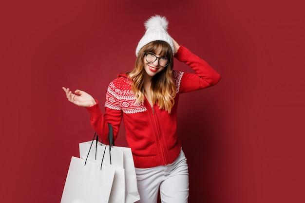 Mooie vrouw in witte wollen hoed en rode winter trui poseren met boodschappentassen Gratis Foto