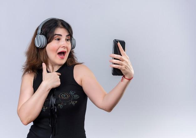 Mooie vrouw in zwarte blouse luisteren naar muziek met koptelefoon slefie met telefoon maken Gratis Foto