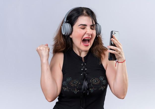 Mooie vrouw in zwarte blouse met telefoon luisteren naar muziek met een koptelefoon en dansen Gratis Foto