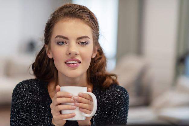Mooie vrouw koffie drinken in de ochtend thuis Gratis Foto