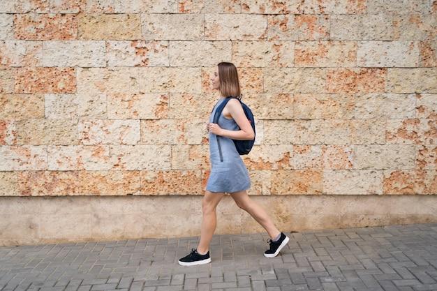 Mooie vrouw lopen met een rugzak in blauwe jurk wandelen in de stad op muur versierd met steen met mariene textuur Gratis Foto