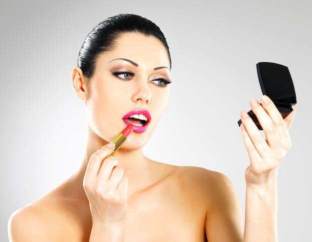 Mooie vrouw maakt make-up roze lippenstift op lippen toe te passen. Gratis Foto