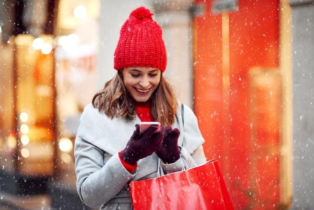 Mooie vrouw met behulp van mobiele telefoon tijdens het winkelen in de winter Gratis Foto