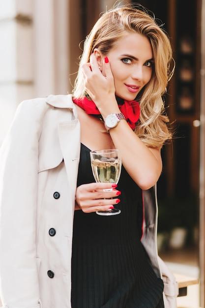 Mooie vrouw met blauwe grote ogen en lichte make-up poseren met plezier tijdens de viering. buiten portret van blije jonge dame met glanzend blond haar champagne drinken op straat. Gratis Foto