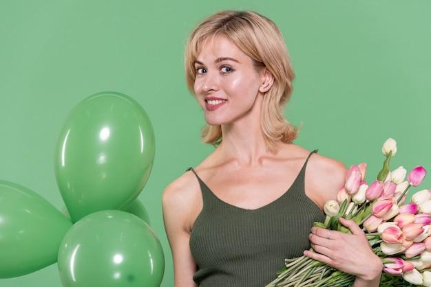 Mooie vrouw met bloemen en ballonnen Gratis Foto