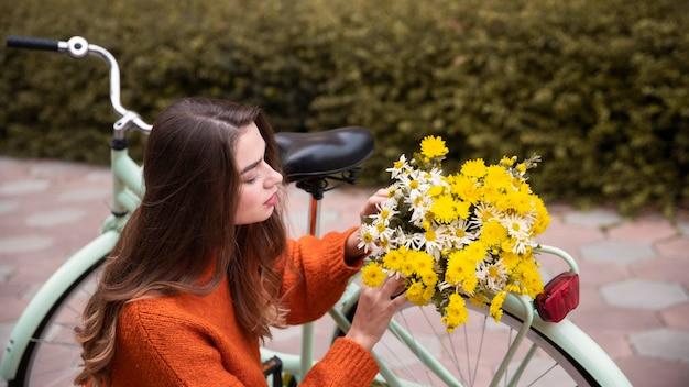 Mooie vrouw met bloemen en fiets buitenshuis Gratis Foto