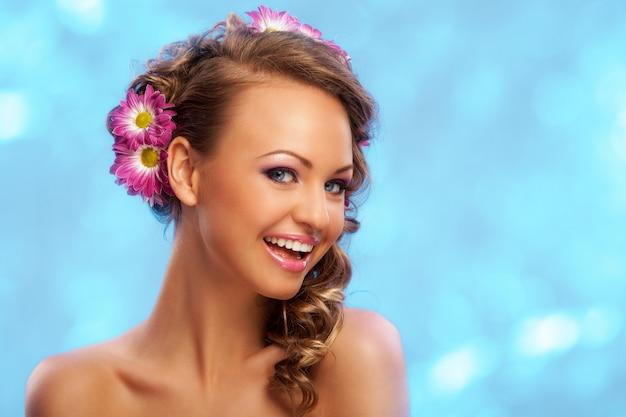 Mooie vrouw met bloemen in haar haar Gratis Foto